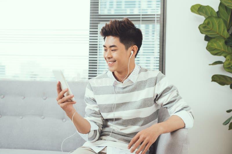 Homme bel asiatique de sourire s'asseyant sur le sofa confortable écoutant le mus photo stock