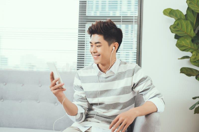Homme bel asiatique de sourire s'asseyant sur le sofa confortable écoutant le mus image libre de droits