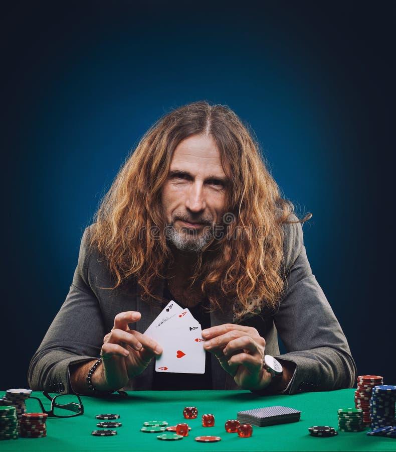 Homme bel aux cheveux longs jouant au poker dans un casino images libres de droits