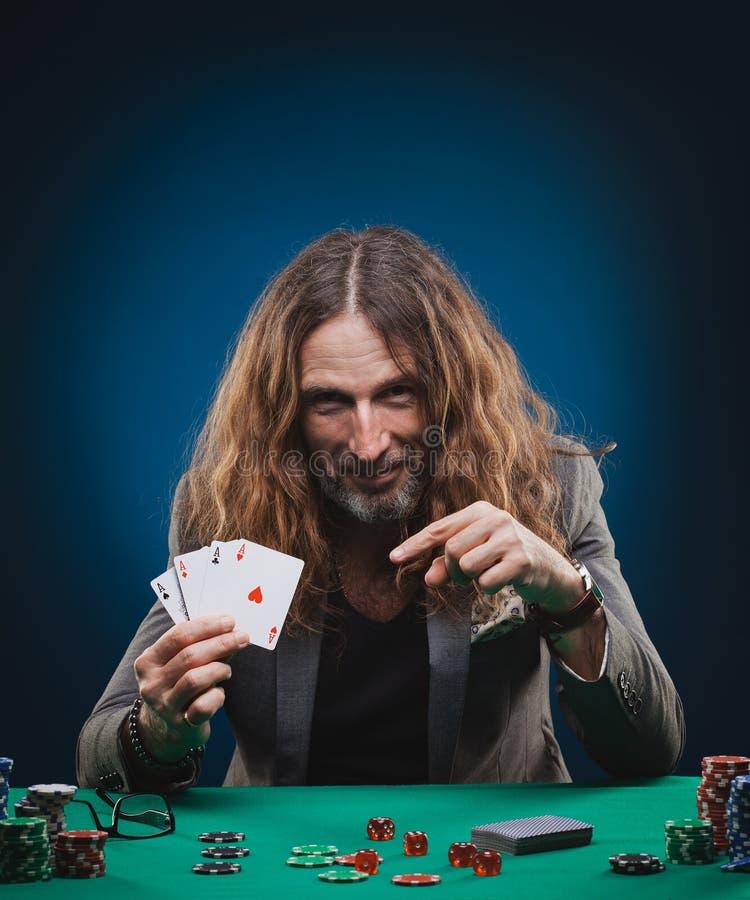 Homme bel aux cheveux longs jouant au poker dans un casino photo libre de droits