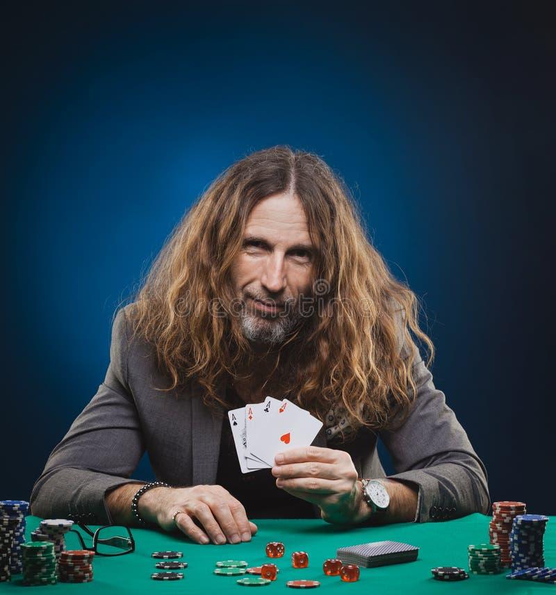 Homme bel aux cheveux longs jouant au poker dans un casino photo stock