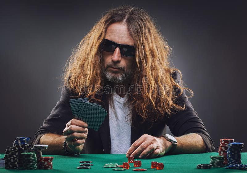 Homme bel aux cheveux longs jouant au poker dans un casino photos stock