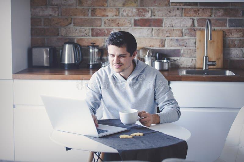Homme bel avec l'ordinateur portatif photographie stock libre de droits