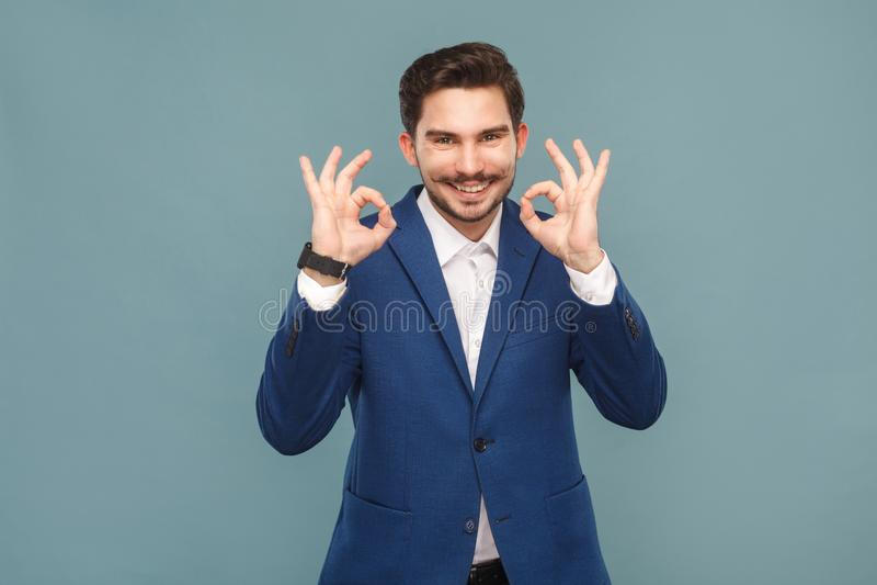 Homme bel avec la moustache montrant le signe correct à l'appareil-photo photographie stock