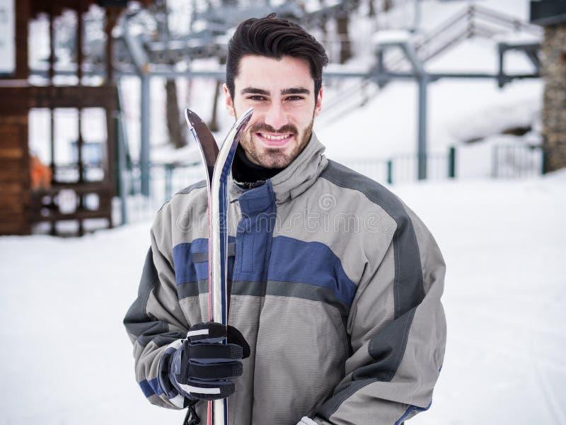 Homme bel avec le ski se tenant dans la neige images libres de droits