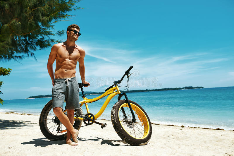 Homme bel avec le vélo Sun se bronzant sur la plage Vacances d'été images libres de droits