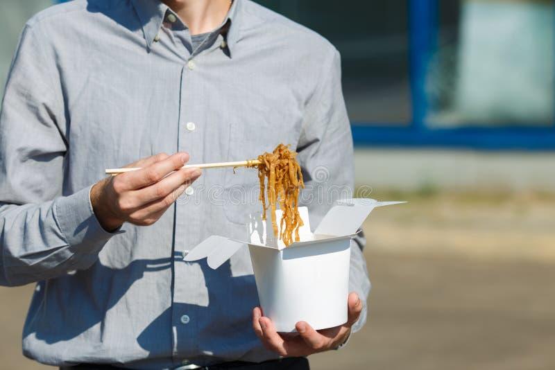 Homme bel avec les nouilles chinoises dans la boîte avec la crevette, les légumes et le sésame avec la sauce de soja Concept de n photographie stock libre de droits