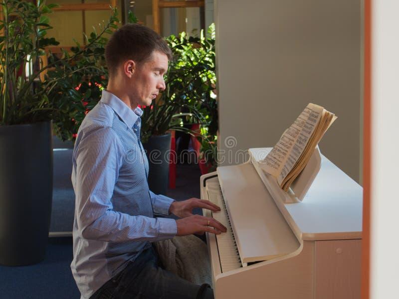 Homme bel avec les yeux fermés tout en jouant le piano à l'intérieur photographie stock libre de droits