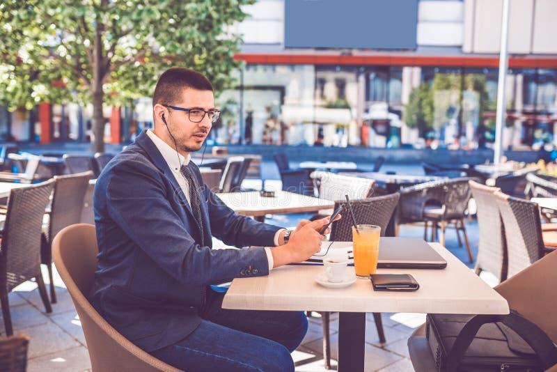 Homme bel ayant le faire appel visuel au téléphone intelligent tout en buvant du café en café de rue photo libre de droits