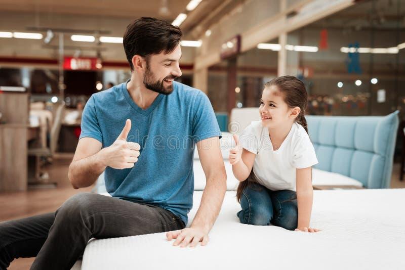Homme bel barbu avec la fille s'asseyant sur le matelas Choix du matelas dans le magasin image libre de droits