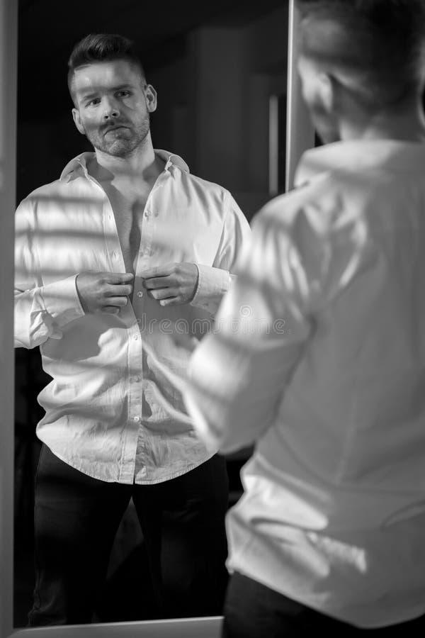 Homme bel boutonnant la chemise images libres de droits