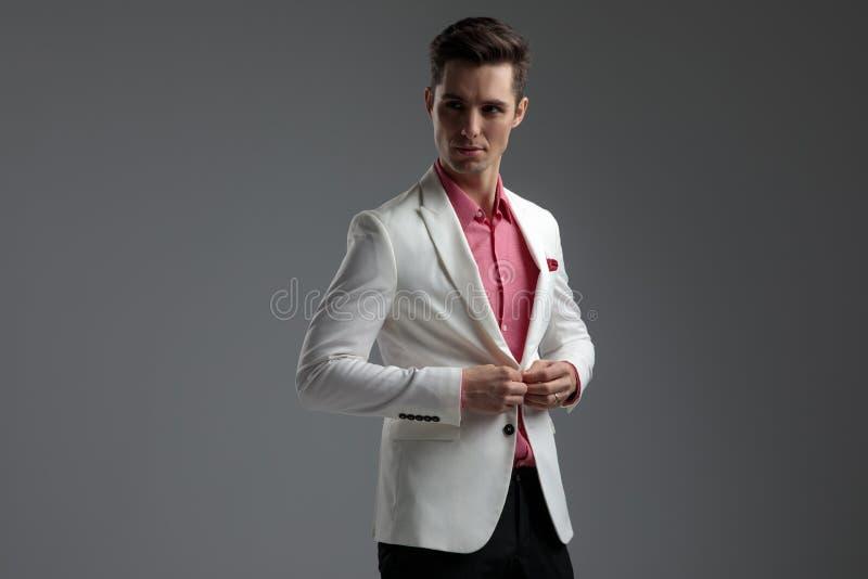 Homme bel boutonnant sa veste de salon tout en regardant loin photographie stock