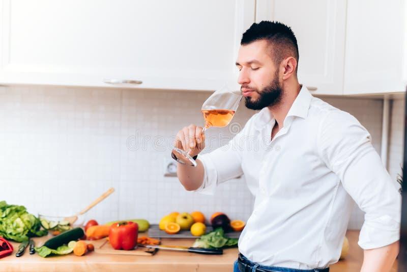 Homme bel buvant un verre de vin rosé pendant la préparation de dîner Cuisinier moderne sirotant du vin tout en faisant cuire la  photographie stock libre de droits