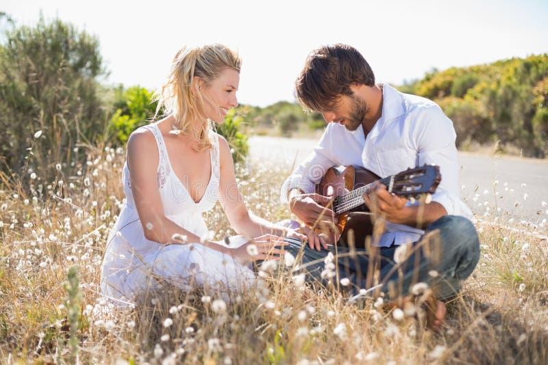 Homme bel chantant une sérénade à son amie avec la guitare photographie stock libre de droits