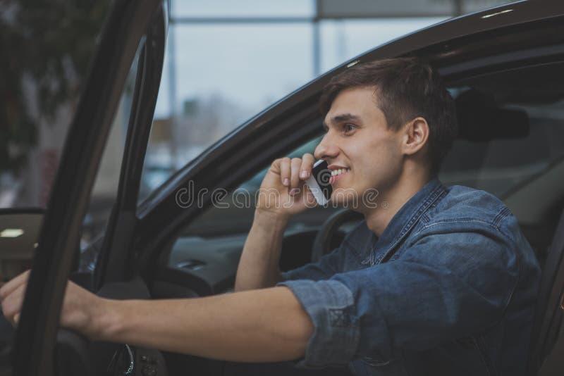 Homme bel choisissant la nouvelle automobile pour acheter photographie stock libre de droits