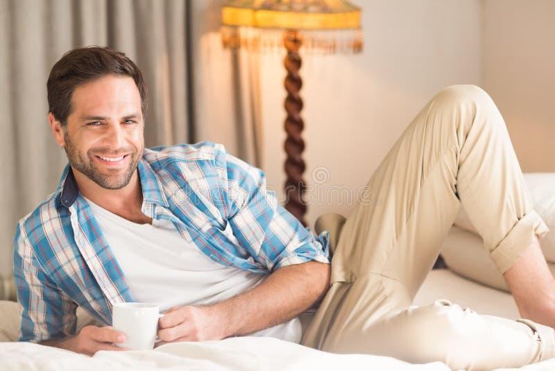 Homme bel détendant sur son lit avec la boisson chaude photographie stock libre de droits