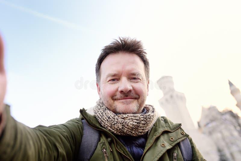 Homme bel d'âge de milddle faisant un selfie d'autoportrait avec le château royal célèbre Neuschwanstein sur le fond photographie stock
