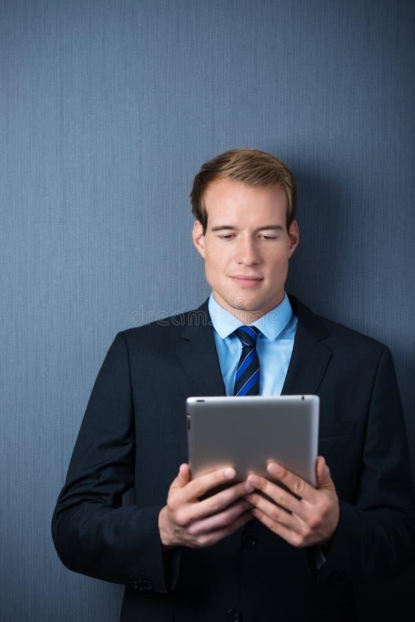 Homme bel d'affaires tenant un comprimé de PC photos stock
