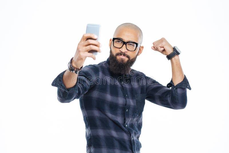 Homme bel d'afro-américain montrant le biceps et faisant le selfie photos stock