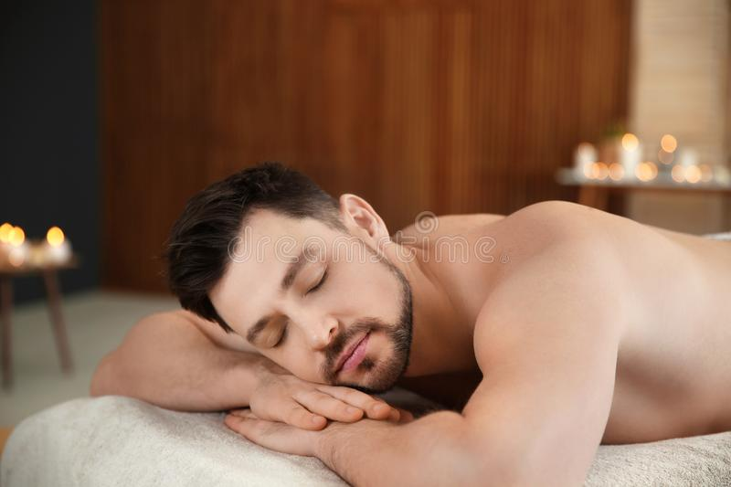 Homme bel d?tendant sur la table de massage image stock