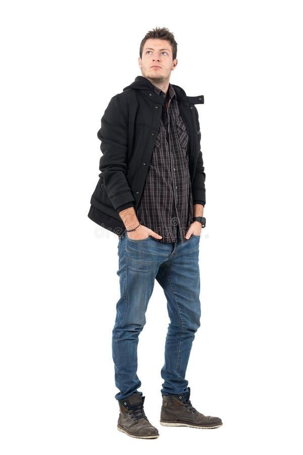 Homme bel dans des bottines de veste et de cuir recherchant sérieusement image libre de droits
