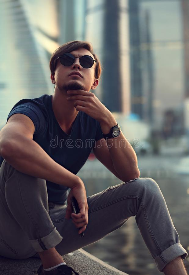 Homme bel dans des lunettes de soleil se reposant et pensant à la vie sur ci photo stock