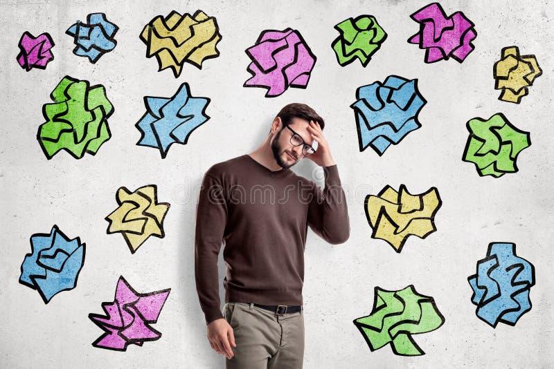 Homme bel dans des vêtements sport se tenant dans le moitié-tour et pensant avec la main sur le front, près du mur avec le multip photo stock