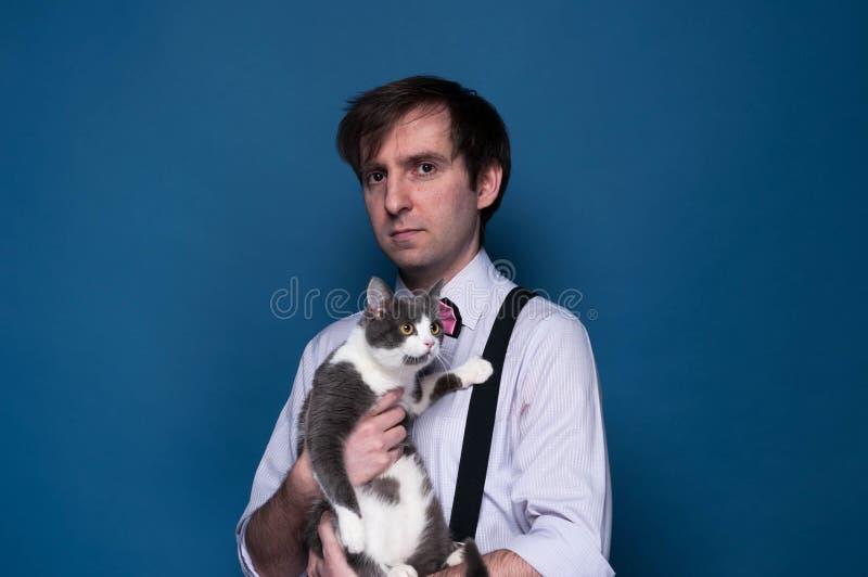 Homme bel dans la chemise, la bretelle et le noeud papillon rose regardant la caméra et tenant le chat gris adorable photos stock