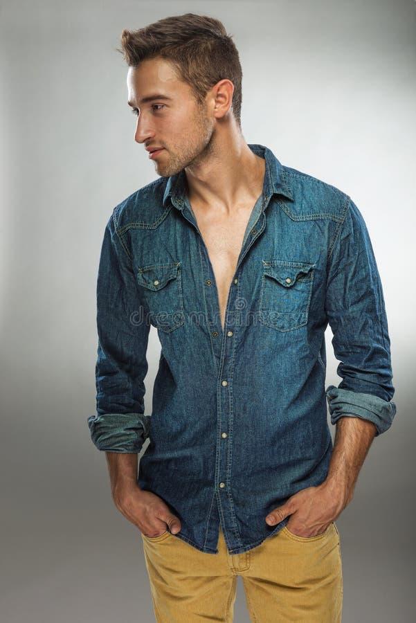 Homme bel dans la robe à la mode posant dans des jeans image libre de droits