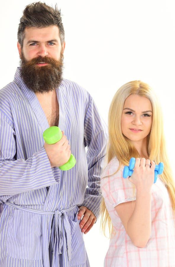 Homme bel dans la robe longue, entraîneur avec la jeune femme attirante dans le pyjama faisant des exercices avec l'haltère, coup photographie stock libre de droits