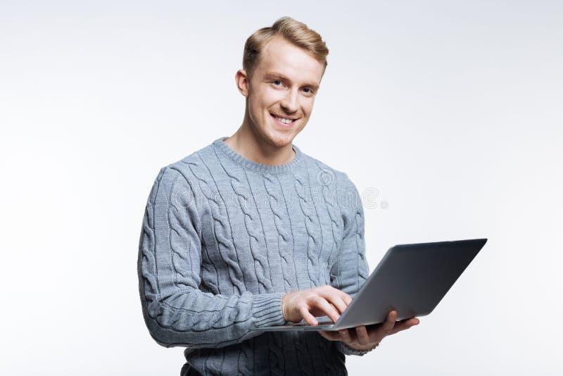 Homme bel dans le chandail gris travaillant sur l'ordinateur portable image stock