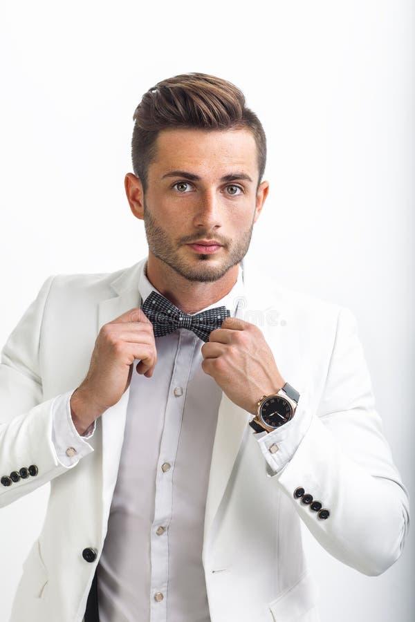 Homme bel dans le costume élégant ajustant son noeud papillon photos libres de droits