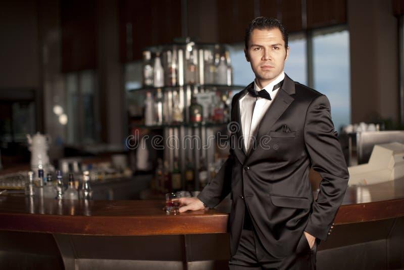 Homme bel dans le smoking au whiskey de fixation de bar photographie stock