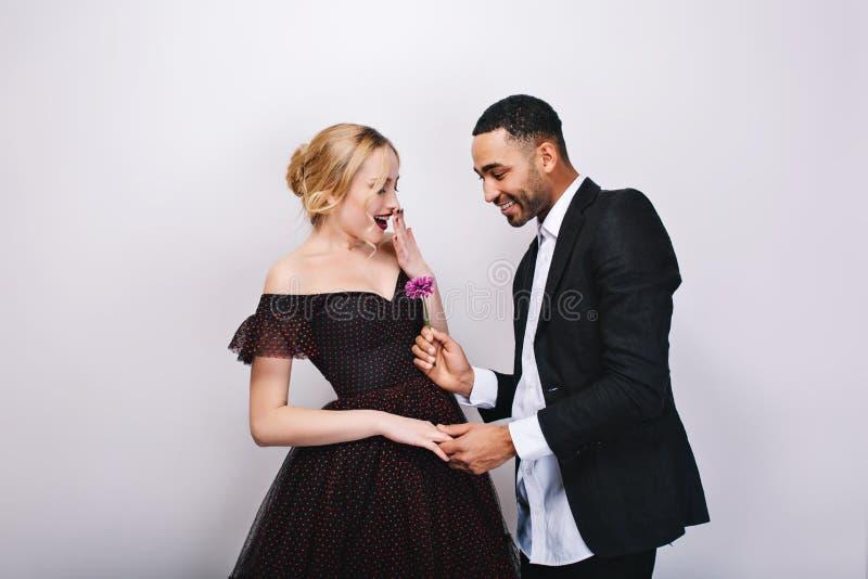 Homme bel dans le smoking donnant la fleur à la belle jeune femme blonde dans la robe égalisante de luxe sur le fond blanc image stock