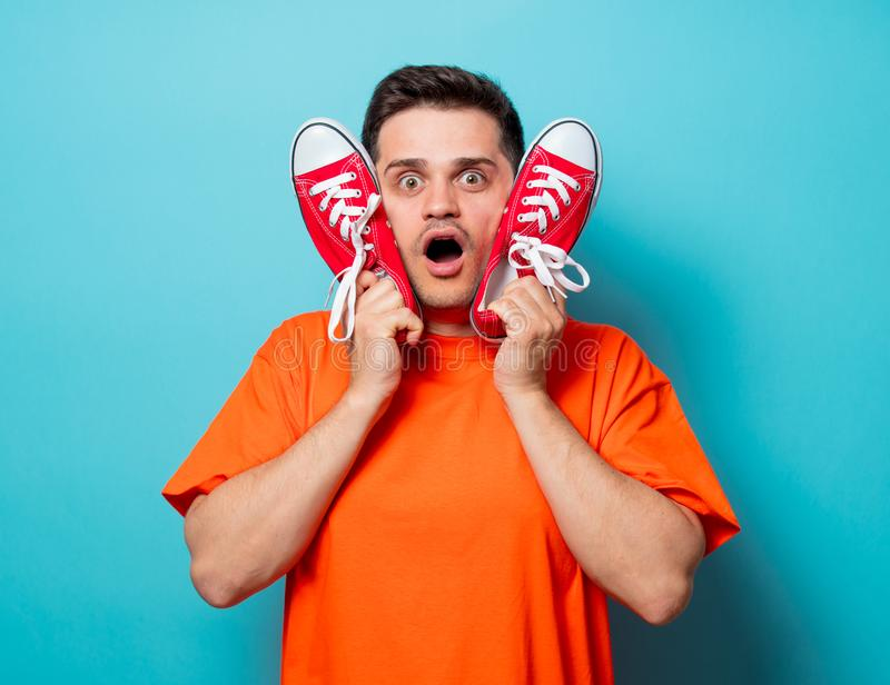 Homme bel dans le T-shirt orange avec les chaussures en caoutchouc rouges photographie stock