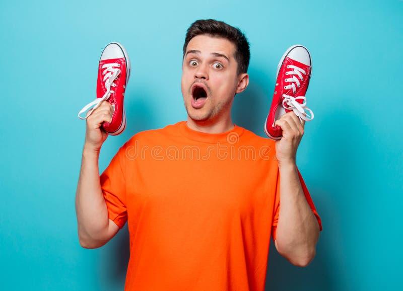 Homme bel dans le T-shirt orange avec les chaussures en caoutchouc rouges photos stock