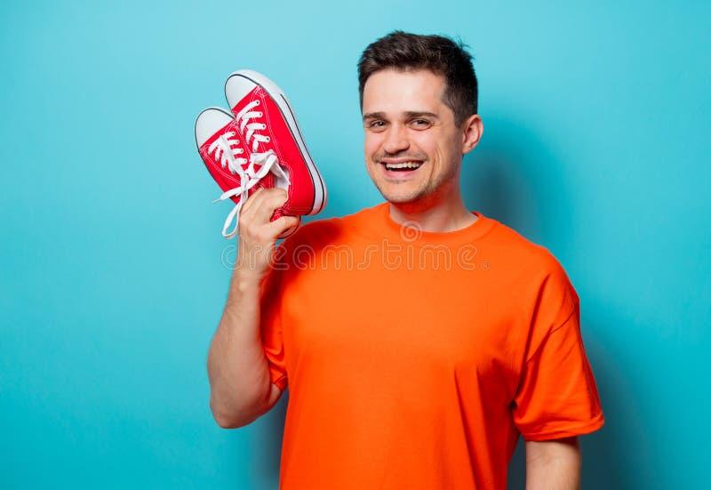 Homme bel dans le T-shirt orange avec les chaussures en caoutchouc rouges image stock