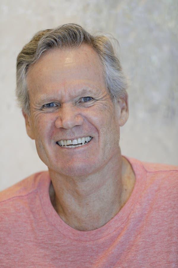 Homme bel dans son 60 ` s souriant à l'appareil-photo images stock