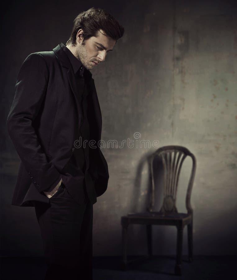 Homme bel dans un costume sur un fond foncé image stock