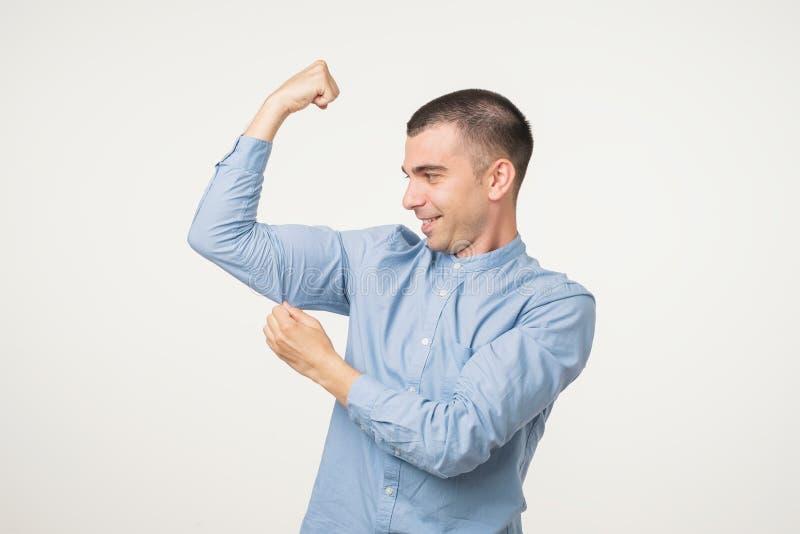 Homme bel de Moyen Âge dans la chemise bleue dirigeant le biceps exprimant la force et la vie saine photos libres de droits