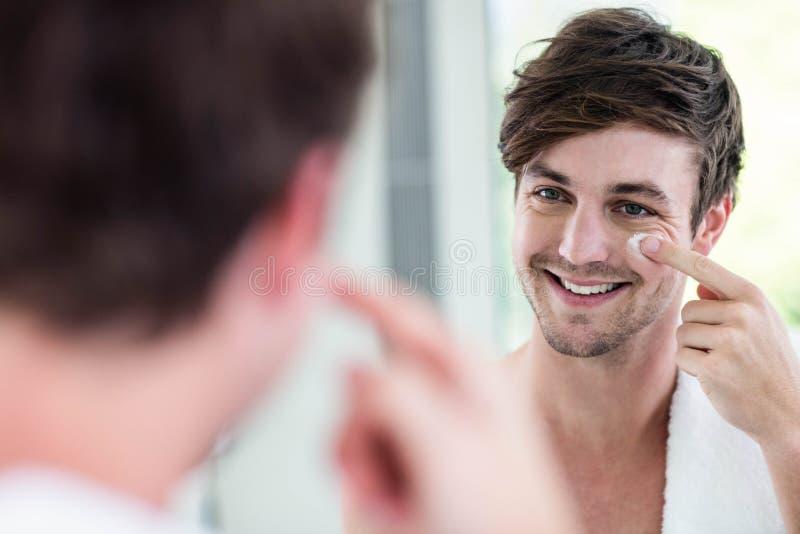 Homme bel de sourire appliquant la crème images libres de droits