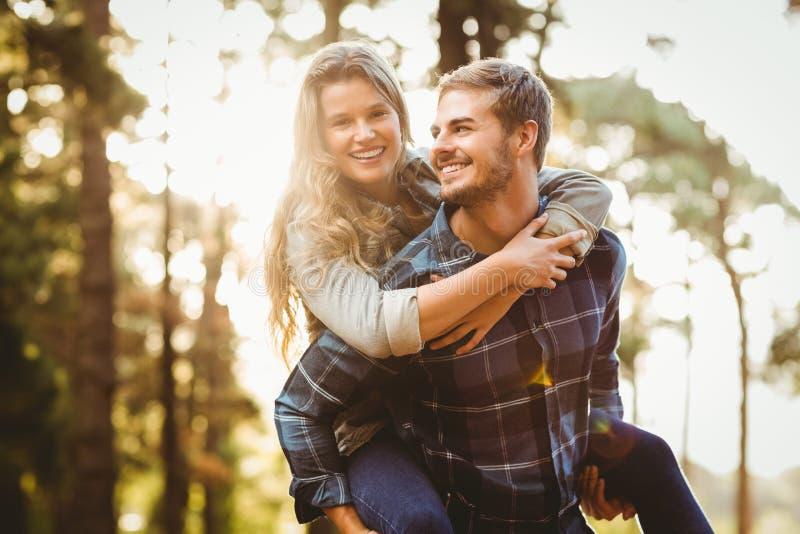 Homme bel de sourire donnant sur le dos à son amie images stock