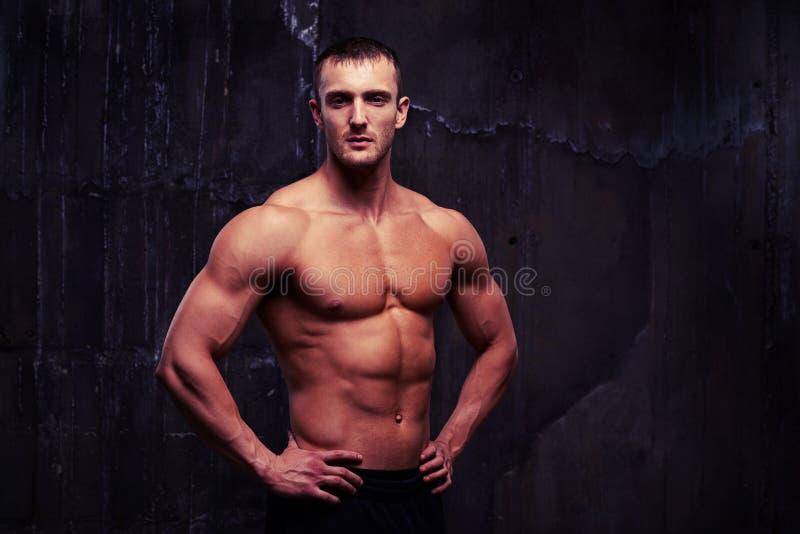 Homme bel de torse nu avec les muscles reliefed tenant le moitié-TU photographie stock libre de droits
