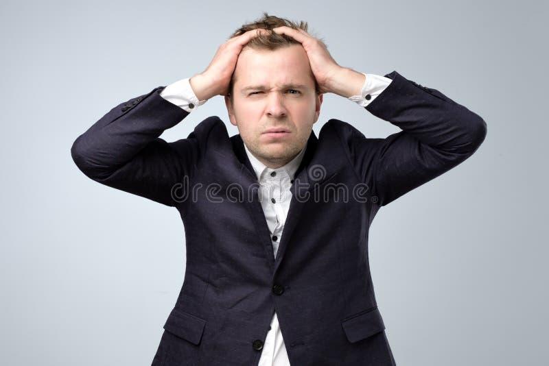 Homme bel douteux dans la position de costume touchant sa tête et regardant le caemra, pensant photos libres de droits