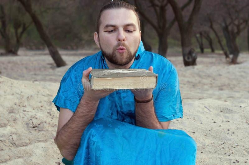 Homme bel en sable de soufflement de kimono bleu de livre photos stock