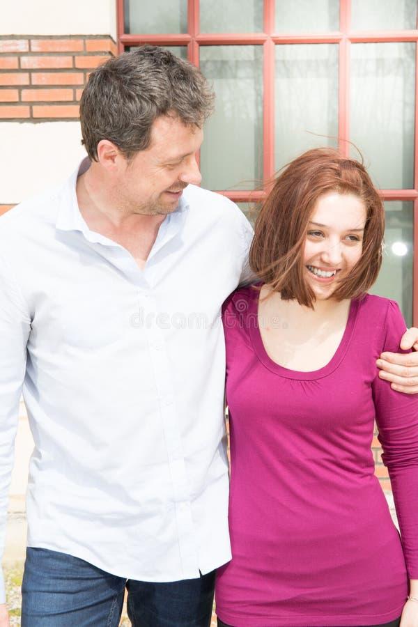 Homme bel et jeune femme étreignant et marchant dans la ville dans l'amour de mode de vie photos stock