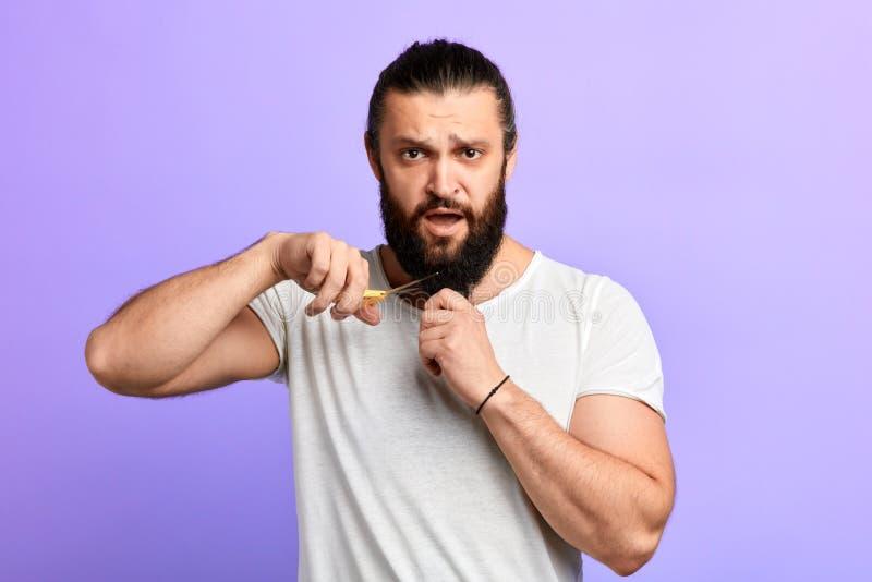 Homme bel fâché coupant sa barbe images stock