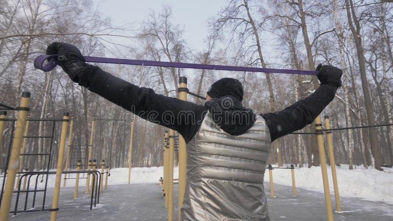 Homme bel faisant l'exercice de séance d'entraînement avec l'extenseur de forme physique sur l'au sol de sports photos libres de droits