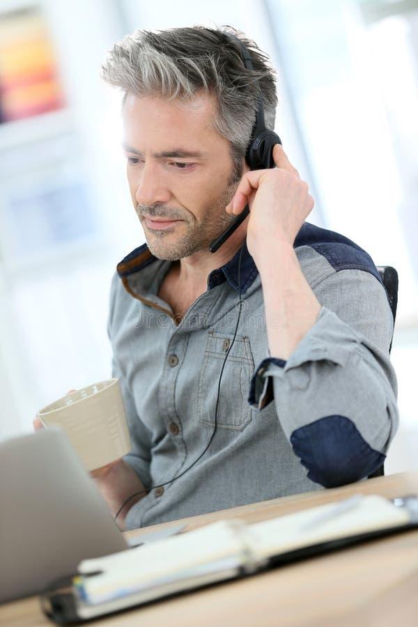 Homme bel faisant un appel visuel sur l'ordinateur portable photos libres de droits
