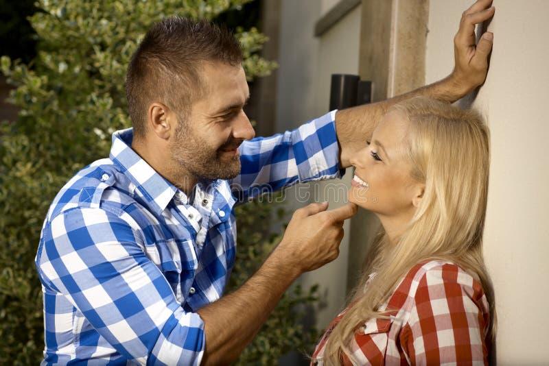 Homme bel flirtant avec la jeune femme dehors image stock